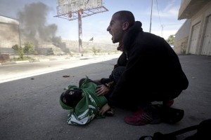 CORRECTION REMOVES REFERENCE TO WHO SHOT THE TEEN, PENDING AN OFFICIAL INVESTIGATION. ADDS THAT THERE WAS ANOTHER TEEN KILLED THE SAME DAY - FILE - In this Thursday, May 15, 2014 file photo, a Palestinian man shouts for help moments after 17-year-old Mohammad Abu Daher, on the ground, was killed during a lull in a confrontation between stone throwers and Israeli troops near the West Bank city of Ramallah. Two rights groups said on June 12, 2014, that preliminary autopsy findings show the Palestinian teen, whose last name is Salameh, and another teen, Nadim Nawara, were killed that day by live ammunition. The Israeli military has denied use of live ammunition, insisting troops only used rubber-coated steel pellets in the incident. (AP Photo/Majdi Mohammed, File)
